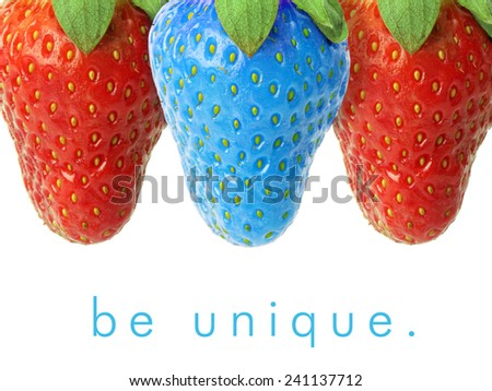 Blue strawberry between red ones. - stock photo