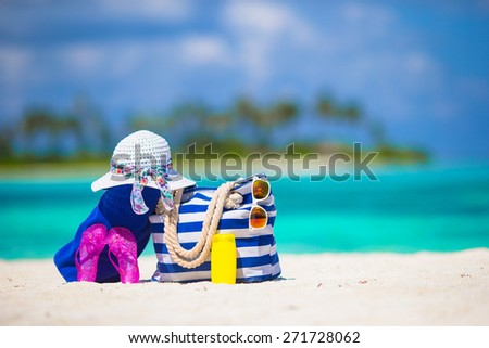 Blue stripe bag, straw white hat, sunglasses, flip flop and sunscreen bottle on tropical beach