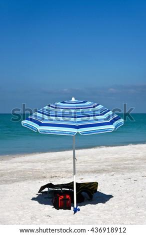 Blue Striped Beach Umbrella and Chair on the Beach - stock photo