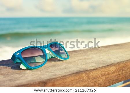 blue sunglasses and sea - stock photo