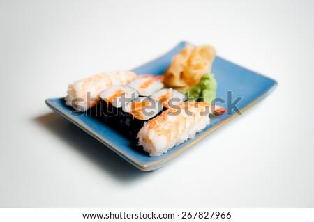 Blue sushi plate with hosomaki and nigiri selective focus on white background - stock photo