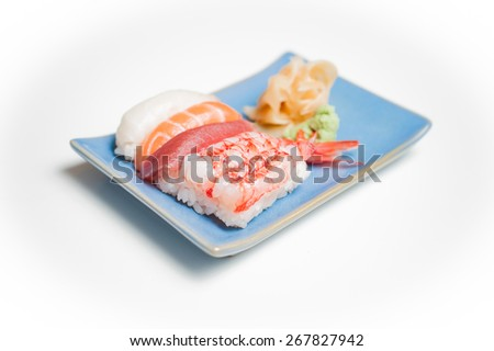 Blue sushi plate with nigiri selective focus on white background - stock photo