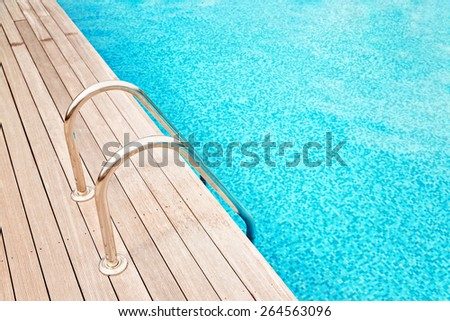 Blue swimming pool with metal hand-rails  and wooden decking  - stock photo