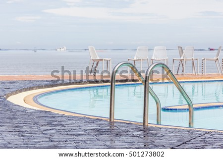 Blue swimming pool with relaxing beach chairs in background.