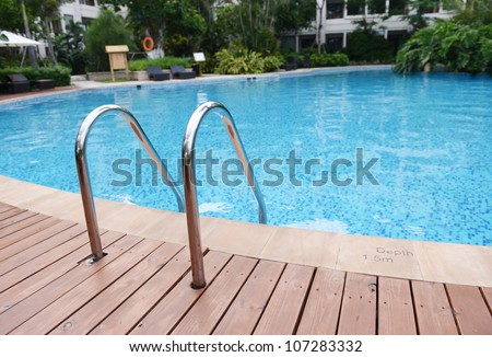 blue swimming pool with stair at hotel. - stock photo