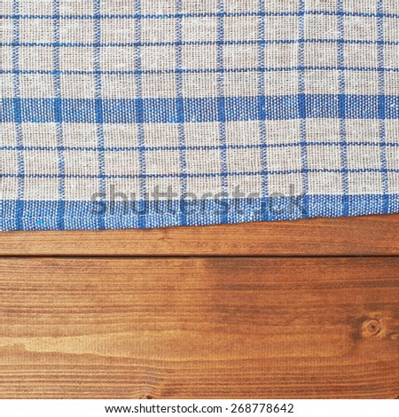 Blue tablecloth or towel over the surface of a brown wooden table - stock photo
