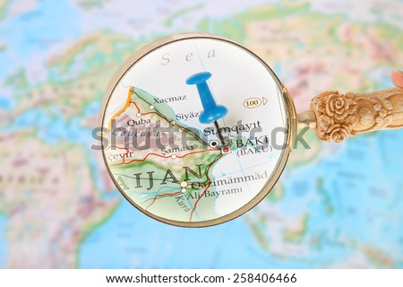 Blue tack on map of Asia with magnifying glass looking in on Baki or Baku, Azerbaijan - stock photo