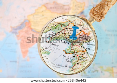 Blue tack on map of Asia with magnifying glass looking in Pyongyang, North Korea - stock photo