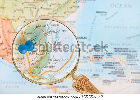 Blue tack on map of Central America with magnifying glass looking in on Belmopan, Belize - stock photo