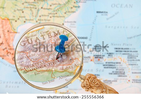 Blue tack on map of Central America with magnifying glass looking in on Guatemala City, Gatemala - stock photo