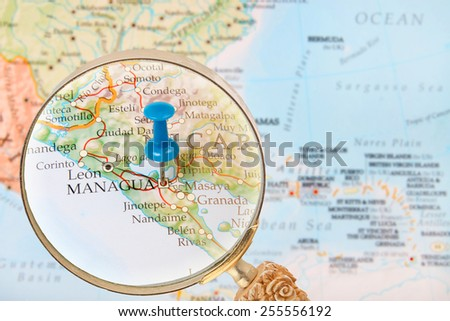 Blue tack on map of Central America with magnifying glass looking in on Managua, Nicaragua - stock photo