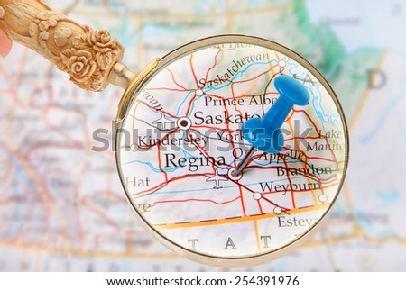 Blue tack on map of central Canada with magnifying glass looking in on Regina, Saskatchewan - stock photo