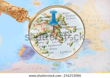 Blue tack on map of Europe with magnifying glass looking in on Athens, Greece - stock photo