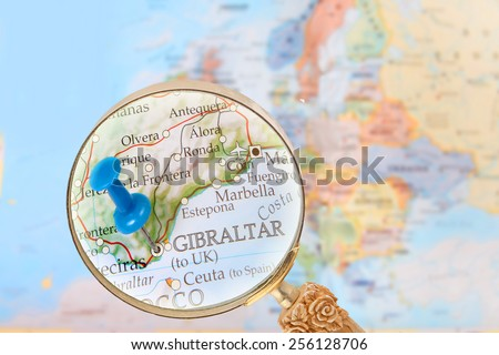 Blue tack on map of Europe with magnifying glass looking in on Gibraltar, United Kingdom - stock photo