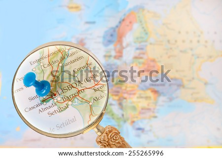 Blue tack on map of Europe with magnifying glass looking in on Lisbon, Portugal - stock photo