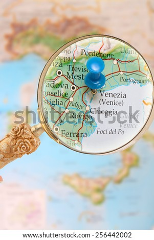 Blue tack on map of Italy with magnifying glass looking in on Venice - stock photo
