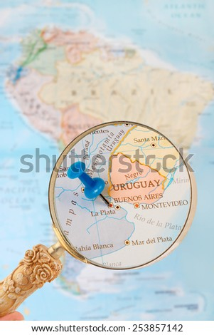 Blue tack on map of South America with magnifying glass looking in on Buenos Aires, the capitol of Argentina - stock photo