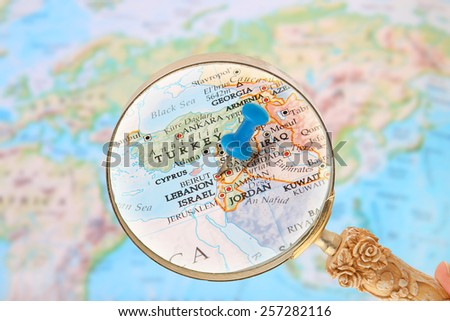 Blue tack on map of  the world with magnifying glass looking in on Beirut, Lebanon,  Middle East in Asia - stock photo
