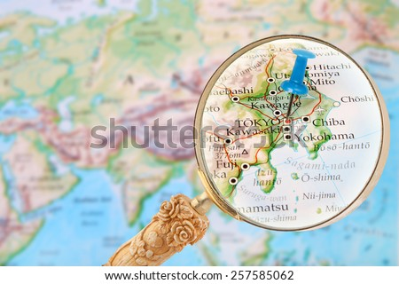 Blue tack on map of the world with magnifying glass looking in on Tokyo, Japan - stock photo