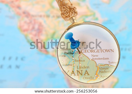 Blue tack on map with magnifying glass looking in on Georgetown, Guyana - stock photo
