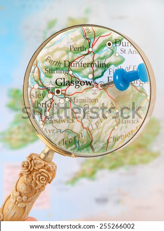 Blue tack on map  with magnifying glass looking in on Glasgow, Scotland, United Kingdom - stock photo
