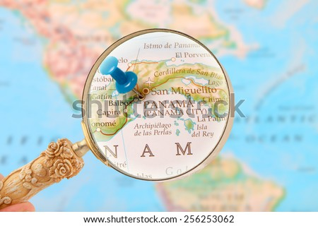 Blue tack on map with magnifying glass looking in on Panama City, Central America - stock photo