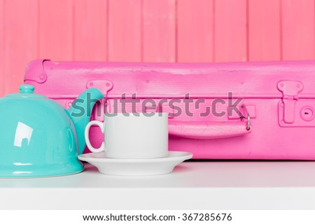 Blue tea pot and home decor on pastel wooden background - stock photo