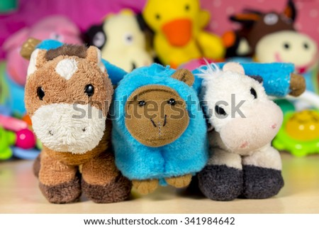Blue teddy monkey embraced to stuffed donkey and cow, in front of other teddy dolls. Friendship.