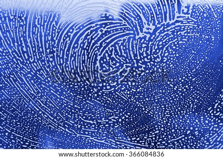 Blue texture with natural soap foam pattern on glass - stock photo