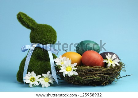 Blue theme Happy Easter scene still life with grass bunny rabbit with rainbow color eggs in a nest with white daisies. - stock photo