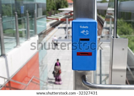 blue ticket validator closeup with train station in background
