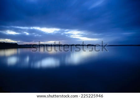 Blue time over the lake after the sunset - stock photo
