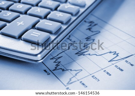 Blue tinted image of calculator and chart - stock photo