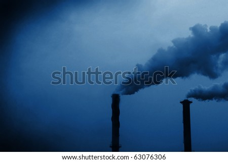 blue tone, dark edges, smoke coming out of smoke stacks. - stock photo