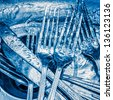 Blue toned image of forks and knives washed on a kitchen sink with a splash of water - stock photo