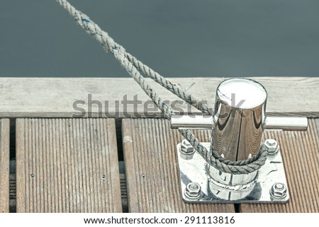 Blue toned marina bollard with rope, marine background with space for text. - stock photo