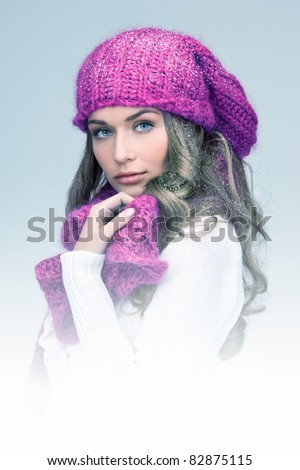 blue-toned picture of beautiful woman in winter hat - stock photo