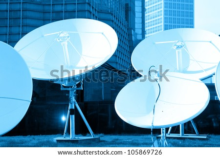blue toned picture of parabolic satellite dish space technology receivers