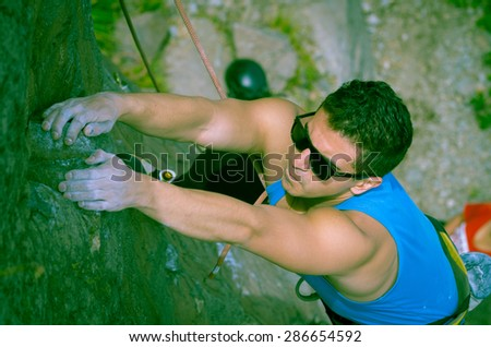 blue toned shot from above angle of man climbing mountain with sunglasses and both arms on rock pulling - stock photo