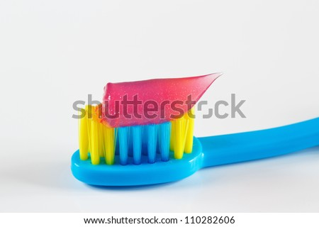Blue toothbrush with pink toothpaste for child on white background - stock photo