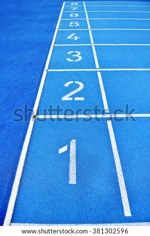 Blue track and field sprint finish line positions with no people - stock photo