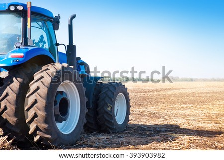 Blue tractor on the background of an empty field and a clear blue sky - stock photo