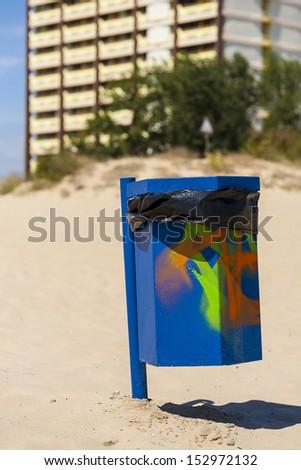 Blue trash basket with graffiti on the beach. - stock photo