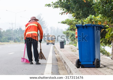 Blue  trash bin with  worker cleaning the road background - stock photo