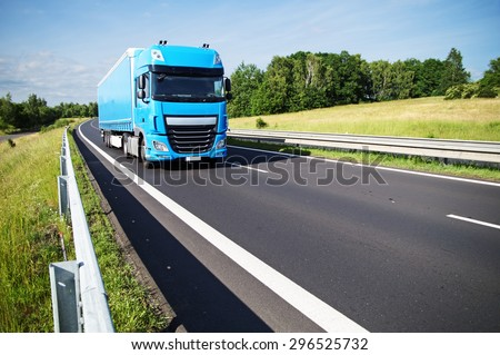 Blue truck on asphalt expressway in the countryside. Sunny day. - stock photo