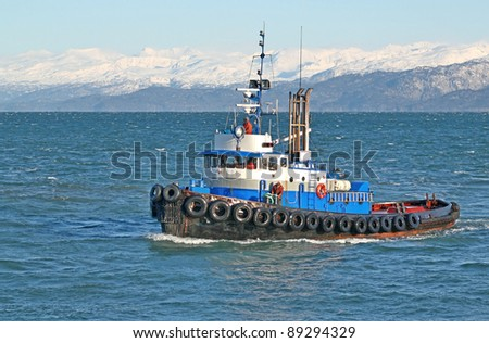Blue tugboat moving through the Kachemak bay in Alaska on a sunny winter day. - stock photo