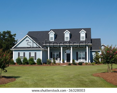 Blue two story board sided residential home with rocking chairs. - stock photo