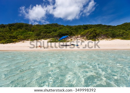 Blue umbrella on picture perfect beach with white sand, turquoise ocean water and blue sky at tropical island in Caribbean