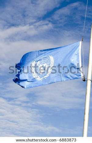 blue UN flag against blue sky - stock photo