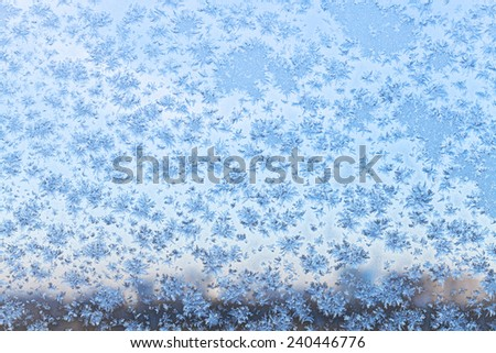 blue urban twilight though snowflakes and frost on window glass in cold winter - stock photo